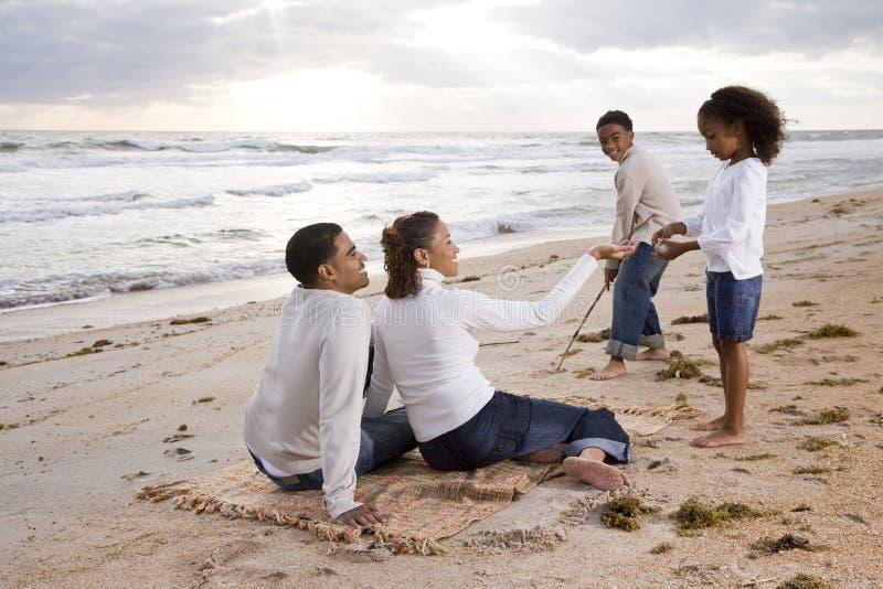 Famille afro-américaine heureuse jouant sur la plage images libres de droits