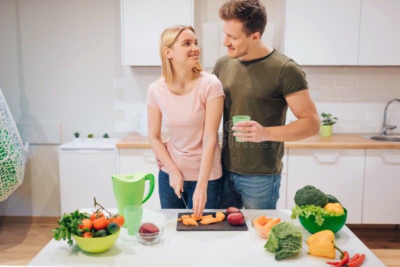 Famille aimante de Vegan faisant cuire des légumes crus dans la cuisine Légume de coupe de jeune femme tandis que son mari boit l image libre de droits