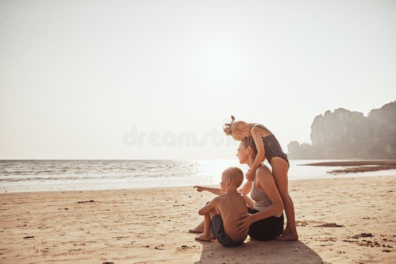 Famille aimante regardant l'océan d'une plage sablonneuse photos stock