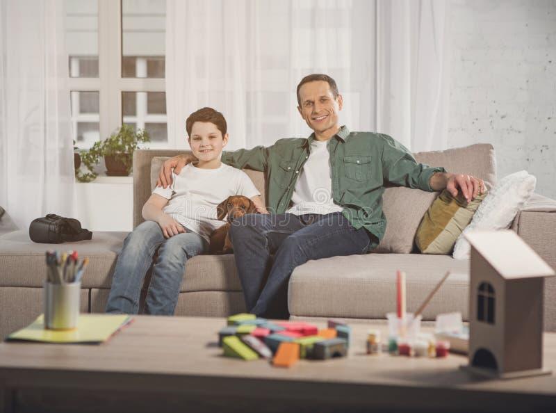 Famille amicale s'asseyant sur le sofa avec l'animal familier photos libres de droits