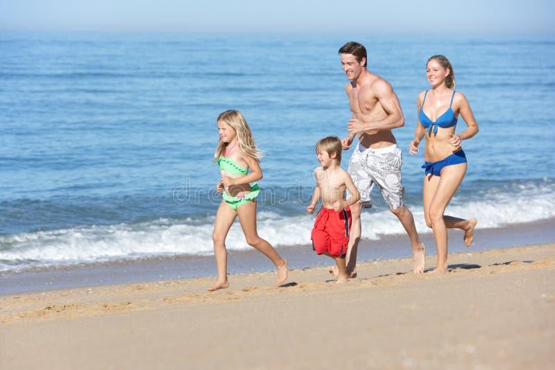 Famille appréciant des vacances de plage fonctionnant le long de la plage images libres de droits