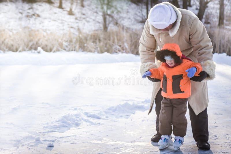 Famille appréciant le patinage de glace sur la piste dehors de patinage en parc neigeux pendant des vacances d'hiver photo stock
