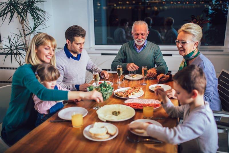 Famille appr?ciant le repas autour de la table ? la maison image libre de droits