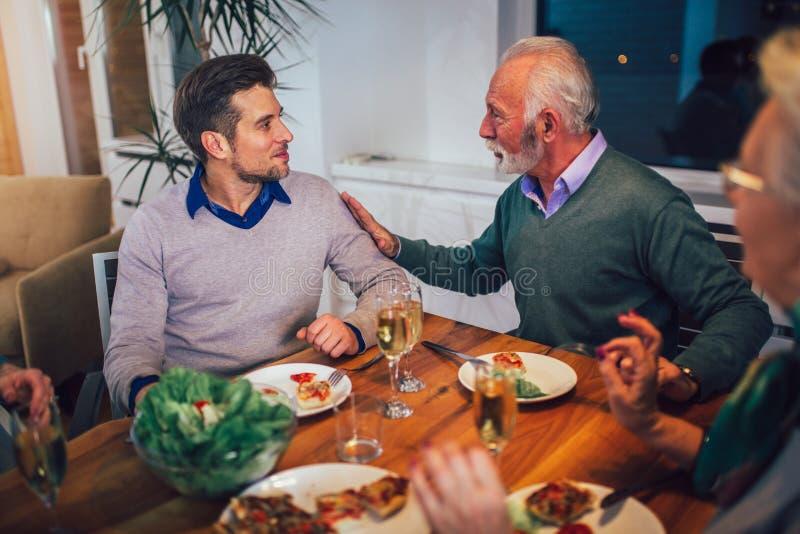 Famille appr?ciant le repas autour de la table ? la maison photographie stock
