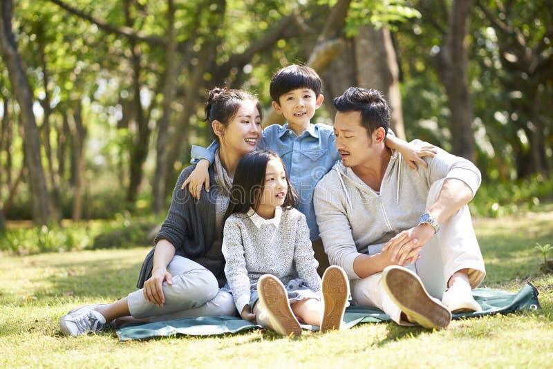 Famille asiatique avec deux enfants causant en parc photo libre de droits
