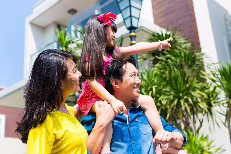 Famille asiatique avec l'enfant se tenant devant la maison images libres de droits