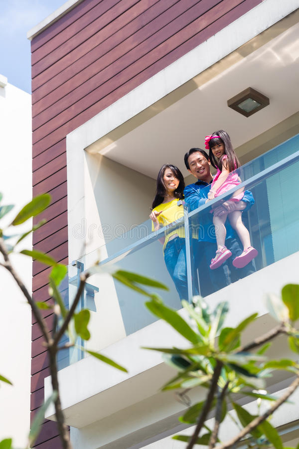 Famille asiatique avec l'enfant se tenant sur le balcon à la maison image libre de droits