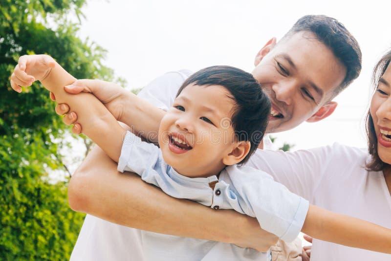 Famille asiatique ayant l'amusement et portant un enfant dans le parc public photos libres de droits