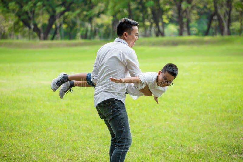 Famille asiatique heureuse Le père et le fils ayant l'amusement jouant et s'étendant donne feindre le vol ensemble le parc papa image stock