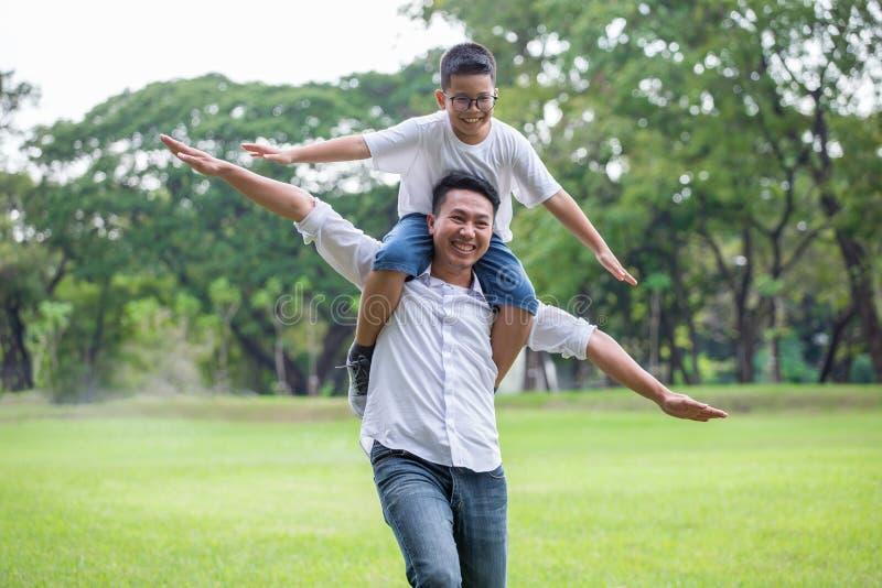 Famille asiatique heureuse Le père et le fils courant, jouant et s'étirant donne ensemble le parc le garçon s'assied sur des épau photographie stock libre de droits
