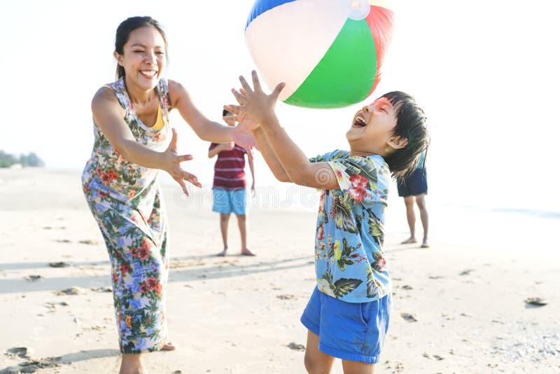 Famille asiatique jouant à la plage images stock