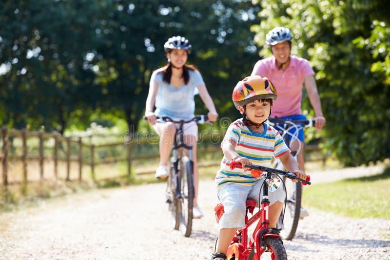 Famille asiatique sur le tour de cycle dans la campagne image stock