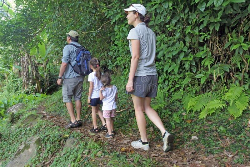 Famille augmentant la voie croisée d'île dans la forêt tropicale d'un tro photographie stock libre de droits