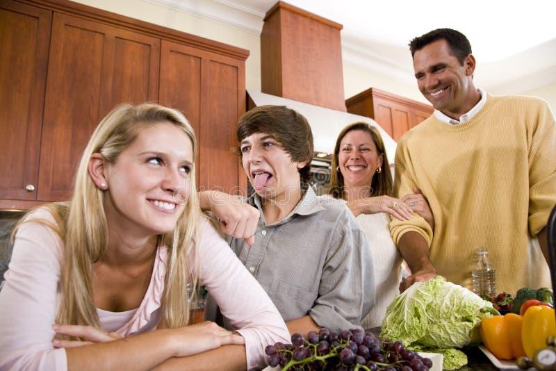 Famille avec des adolescents effectuant des visages dans la cuisine photographie stock libre de droits