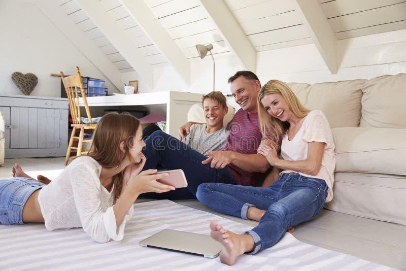 Famille avec des adolescents employant la technologie à la maison photos stock