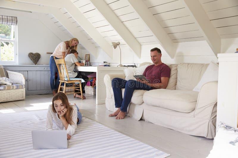 Famille avec des adolescents employant la technologie à la maison photo stock