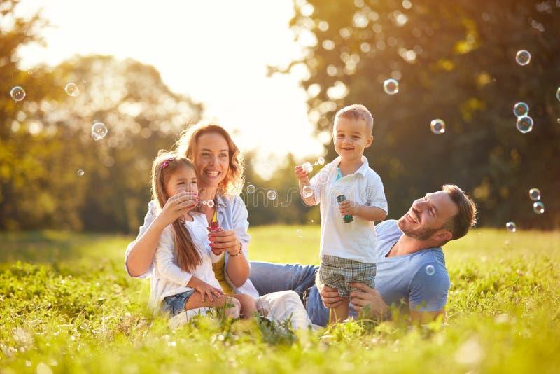 Famille avec des bulles de savon de coup d'enfants photographie stock