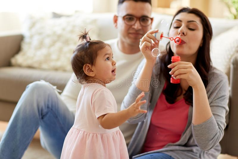 Famille avec des bulles de savon jouant à la maison photos libres de droits