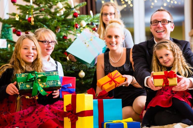 Famille avec des cadeaux de Noël sous l'arbre photographie stock