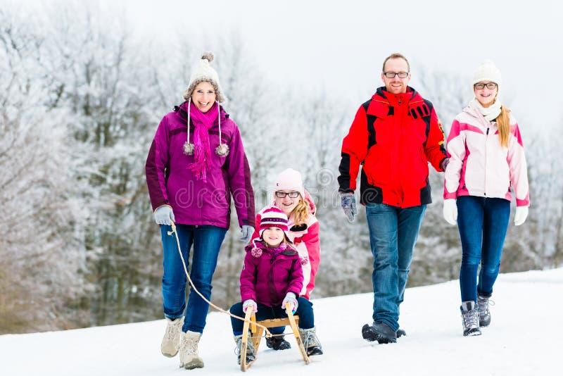 Famille avec des enfants ayant la promenade d'hiver dans la neige photo stock
