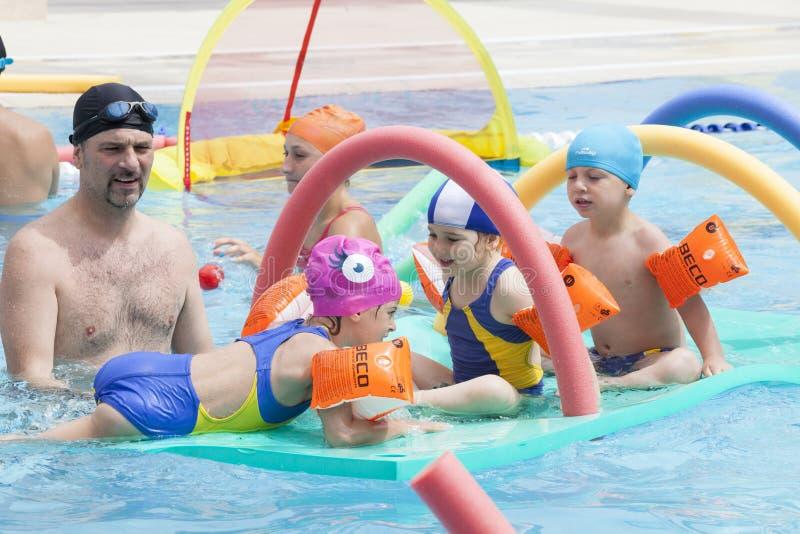 Famille avec des enfants jouant dans la piscine photos stock