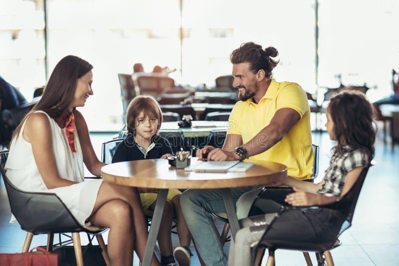 Famille avec deux enfants ayant le grand temps dans un café après boutique photographie stock libre de droits