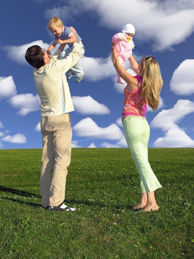 Famille avec deux enfants sur le ciel bleu avec des nuages photo libre de droits