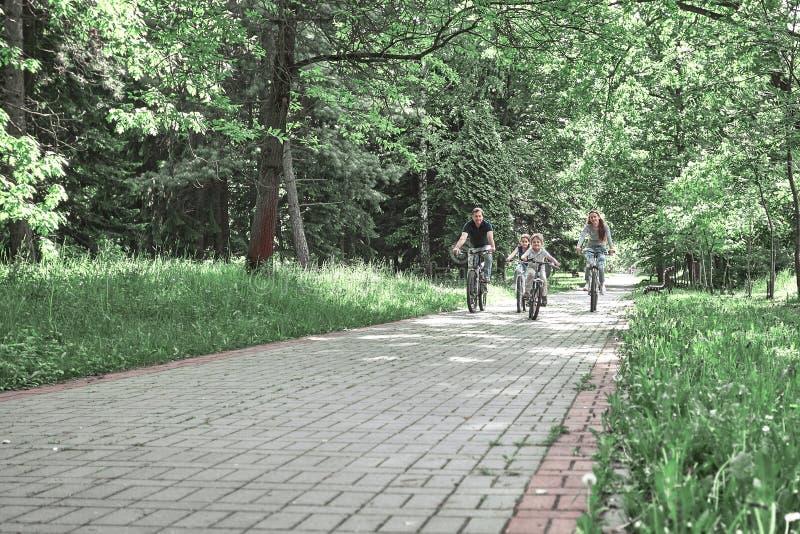 Famille avec deux enfants sur un tour de vélo en parc de ville photo libre de droits