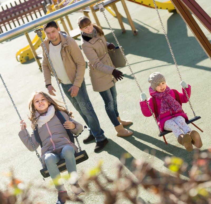 Famille avec deux filles ayant l'amusement sur des oscillations dehors images stock