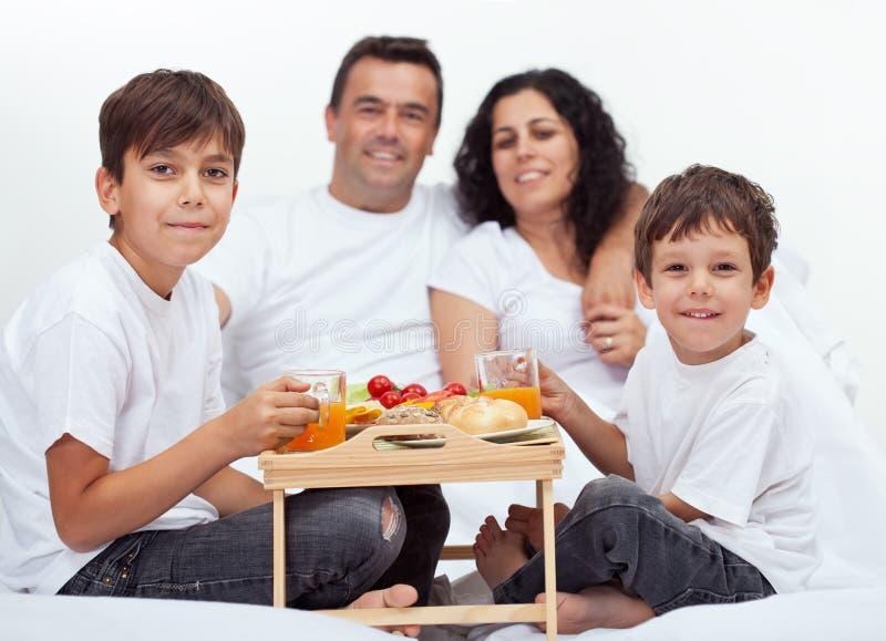Famille avec deux garçons prenant le petit déjeuner dans le lit photo stock