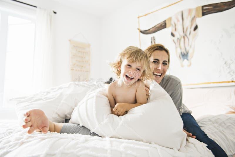 Famille avec l'enfant ayant l'amusement sur le lit avec le combat d'oreiller photos stock