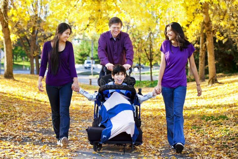 Famille avec l'enfant handicapé dans le fauteuil roulant marchant parmi l'automne le image libre de droits
