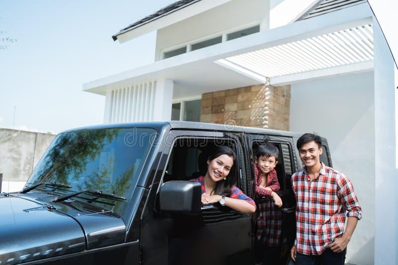 Famille avec l'enfant s'asseyant dans une voiture dans le port de voiture de leur maison photos stock