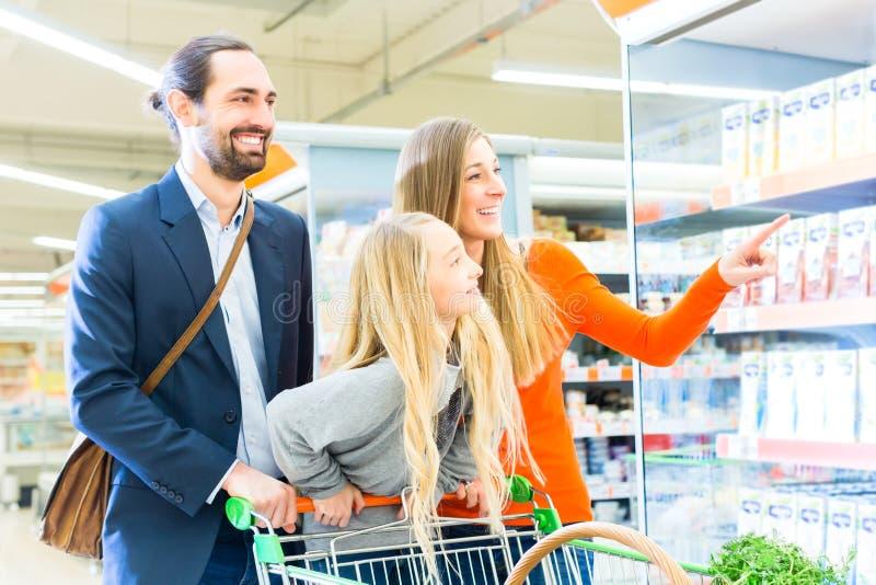 Famille avec le caddie dans le supermarché photo stock