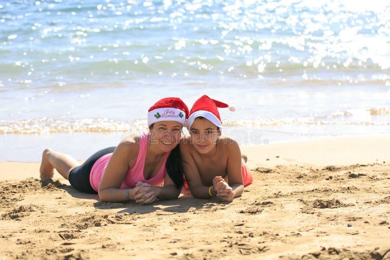 Famille avec le chapeau de Santa sur la plage photographie stock