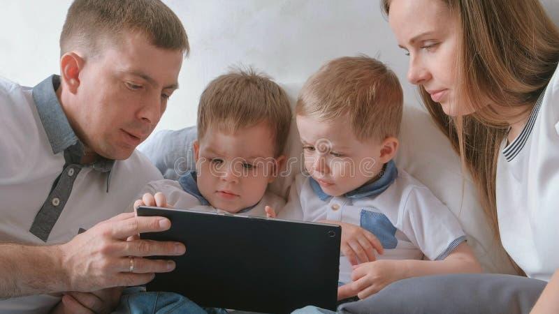 Famille avec le comprimé Maman, papa et deux enfants en bas âge de jumeaux de fils regardant la bande dessinée le comprimé se tro images libres de droits