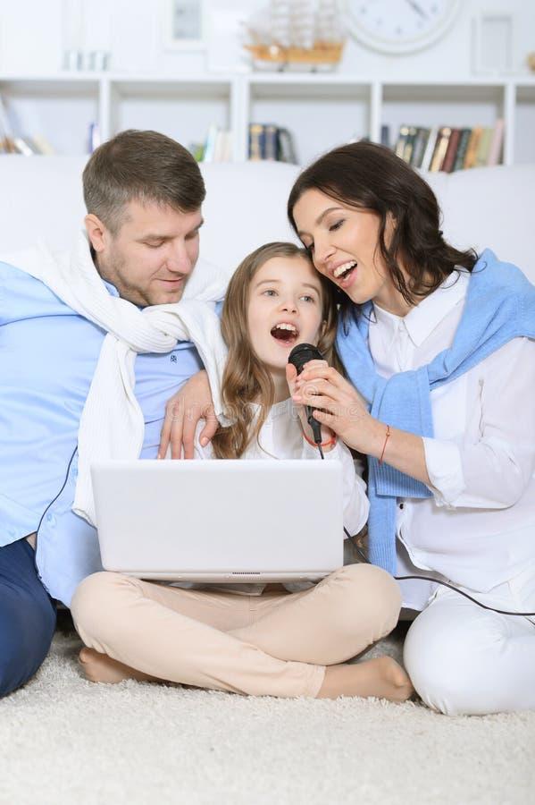 Famille avec le karaoke de chant de fille images libres de droits