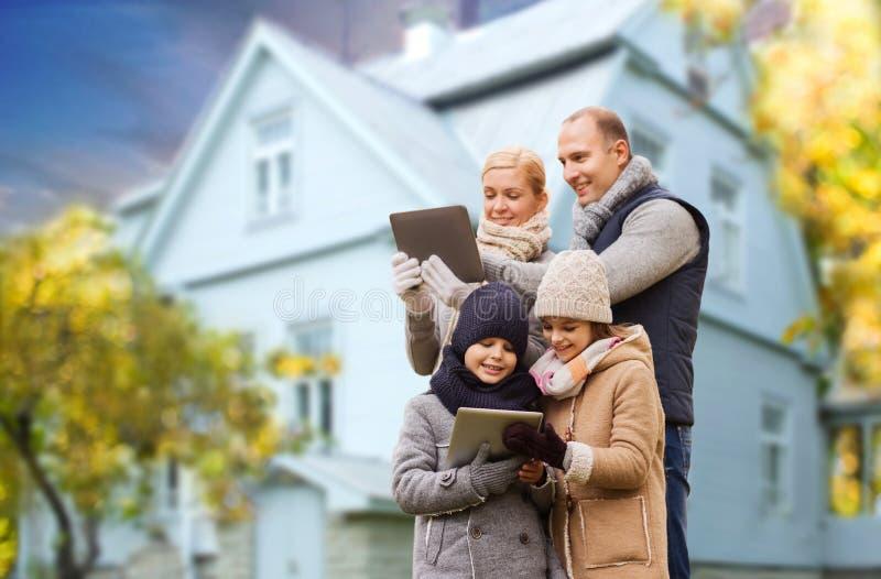 Famille avec le PC de comprimé au-dessus de la maison vivante en automne images stock