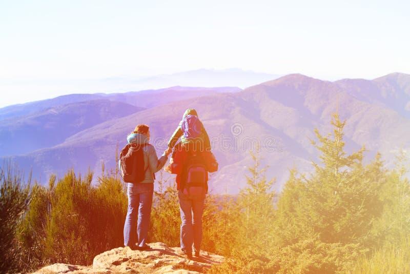 Famille avec le petit enfant trimardant en montagnes photos libres de droits
