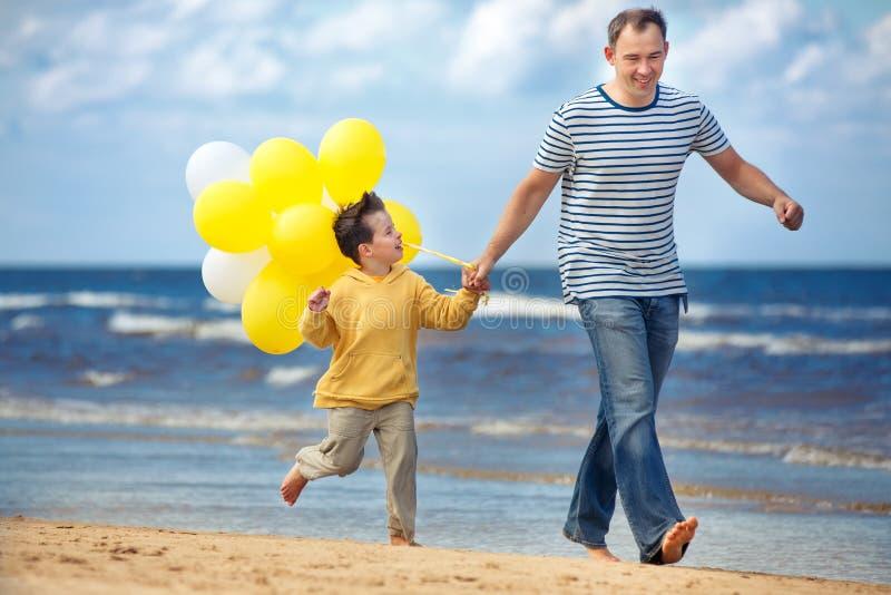 Famille avec les ballons jaunes jouant sur la plage images stock