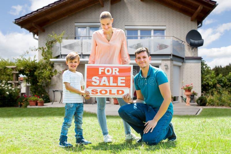 Famille avec un signe de vente en dehors de leur maison photos libres de droits