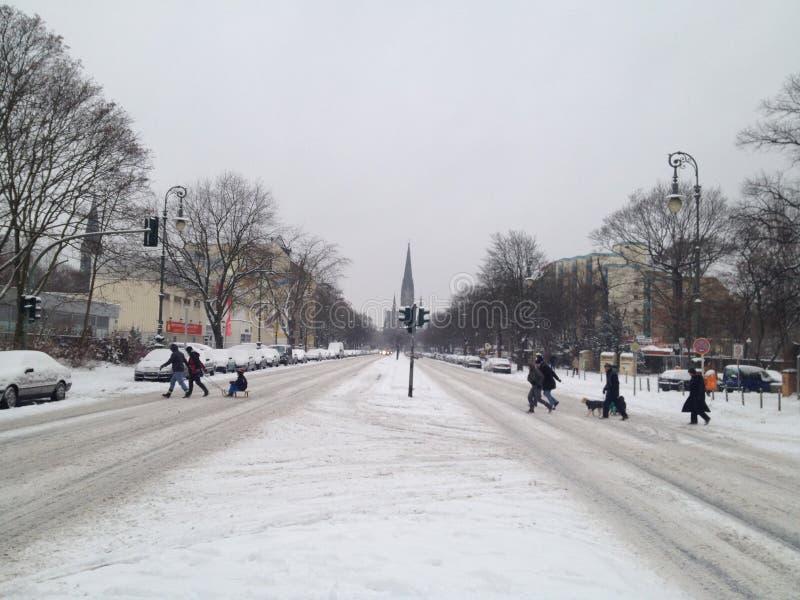 Famille avec un traîneau traversant une rue couverte par neige avec l'église dstern de ¼ de SÃ à l'arrière-plan images stock