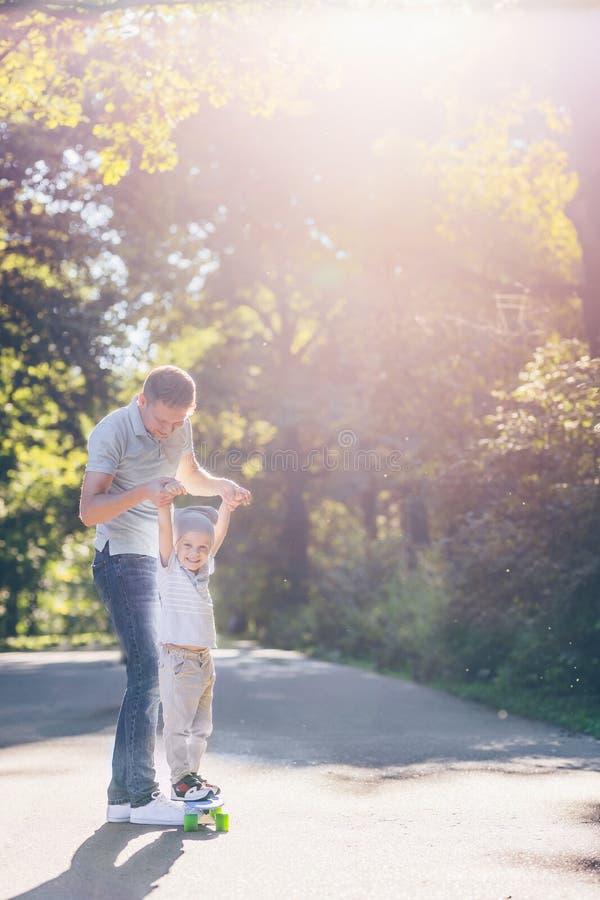 Famille avec une planche à roulettes dehors image libre de droits