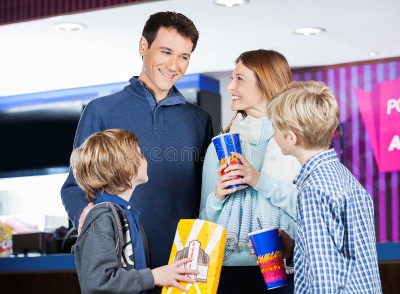 Famille ayant des casse-croûte au stand de concession de cinéma image stock