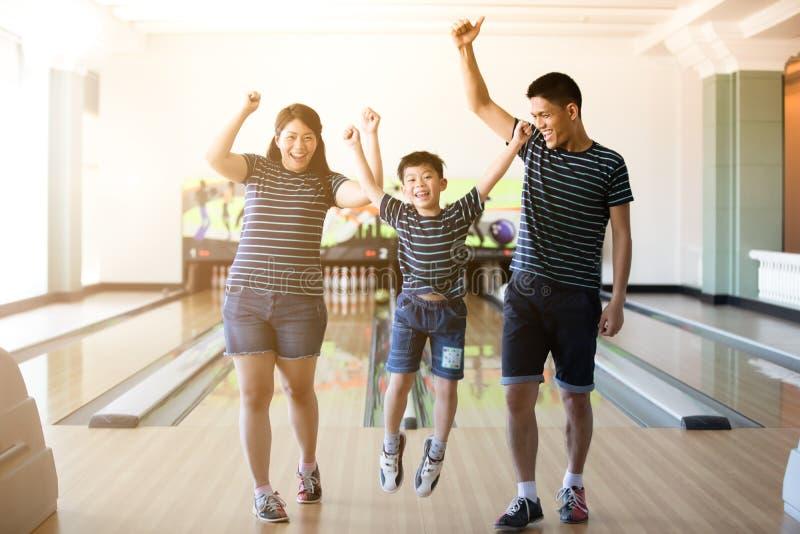 Famille ayant l'amusement au club de bowling après la boule de bowling de quilles, b photo libre de droits