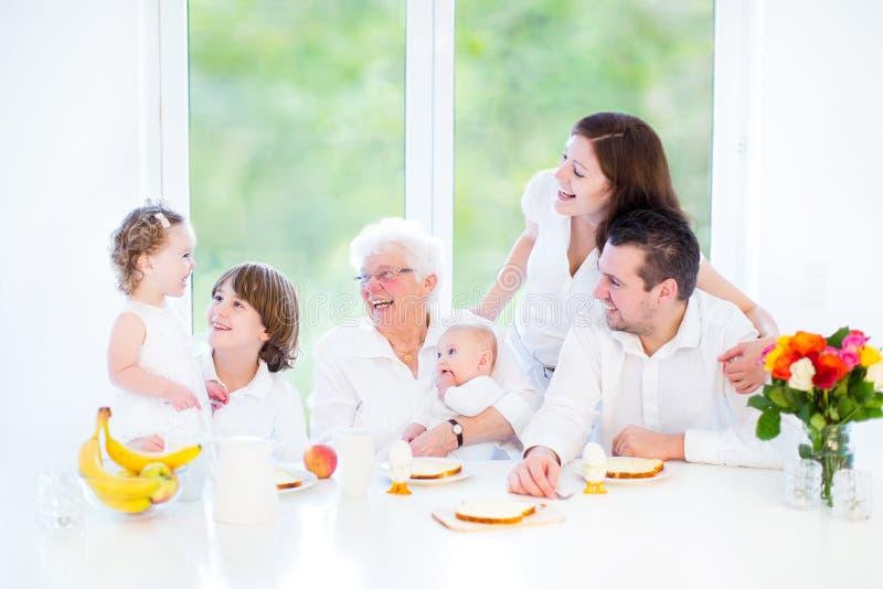 Famille ayant l'amusement au petit déjeuner avec la grand-mère photo libre de droits