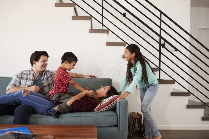 Famille ayant l'amusement se trouvant sur Sofa At Home Together images libres de droits