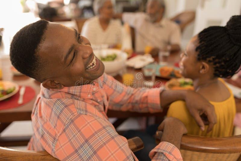 Famille ayant l'amusement sur la table de salle à manger à la maison image libre de droits