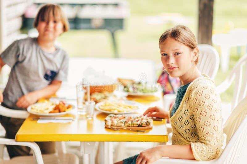 Famille ayant l'extérieur de déjeuner sur une terrasse images libres de droits