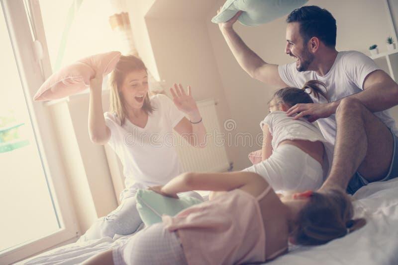 Famille ayant le combat d'oreiller drôle sur le lit photographie stock